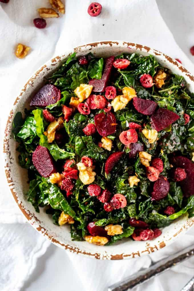 Close up overhead photo of a Kale Beet Salad in a rustic white bowl.
