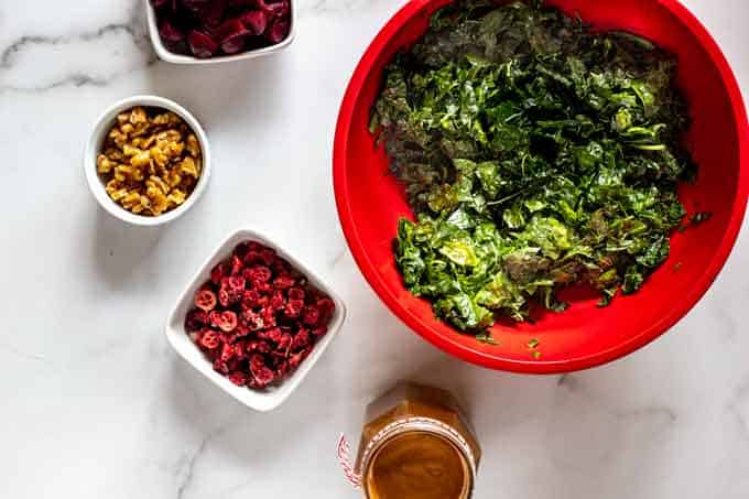 Phot of a red bowl with massaged kale with a jar of balsamic vinaigrette and white bowls with cranberries, pecans, and roasted beets next to it.
