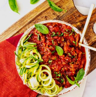 Square overhead photo of Mushroom Bolognese in a white rustic bowl sitting on a wooden cutting board garnished with basil.