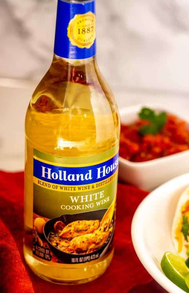 Bottle of Holland House White Cooking Wine on a burgundy napkin.