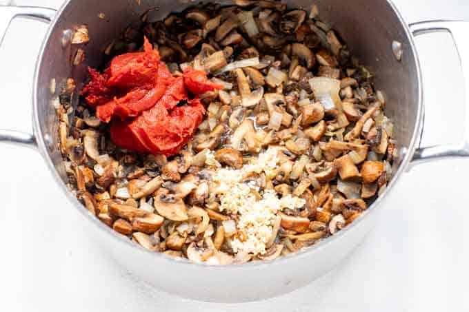 Photo of large pot with mushrooms, onions, tomato paste, and garlic in it.