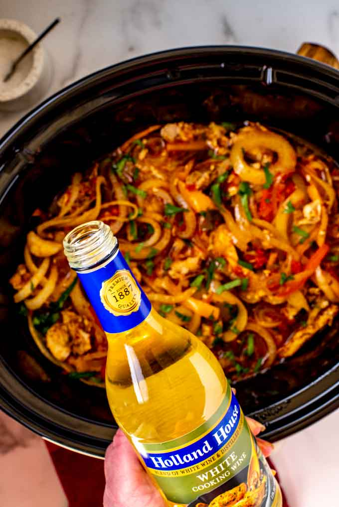 Holland House White Cooking Wine being poured into a crockpot full of chicken fajitas.