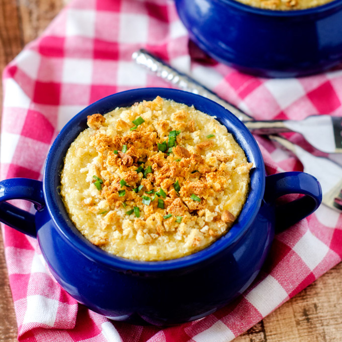 Square photo of quinoa mac and cheese in a blue crock on a checkered cloth napkin.
