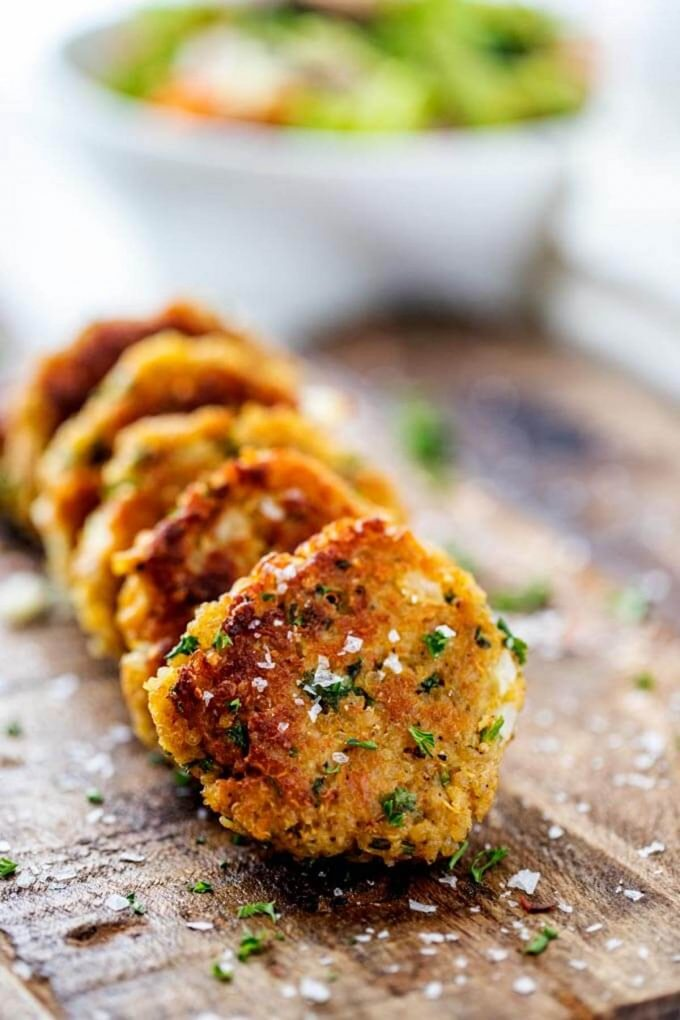 Photo of five quinoa patties lined up on a dark cutting board with a salad blurred in the background.
