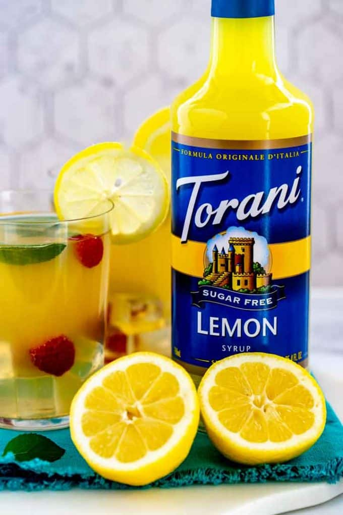 Torani Sugar Free Lemon Syrup with a halved lemon in front of it.