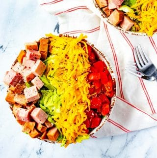 Square overhead photo of a salad in a rustic bowl with ham, cheese, tomato and romaine on a white napkin with thin red stripes.