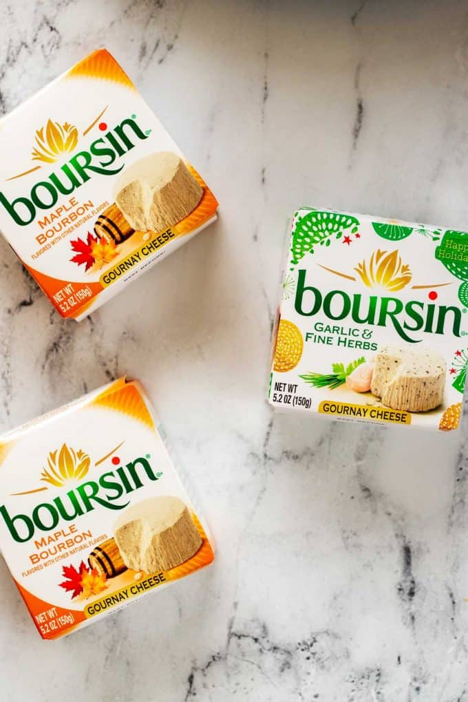 Three packages of Boursin cheese on a white background.