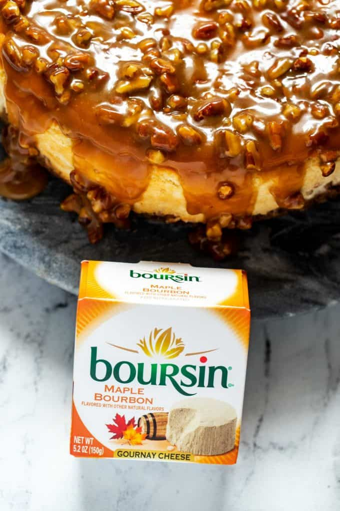 Close up photo of Boursin Maple Bourbon Gournay Cheese sitting in front of a Maple Cheesecake.