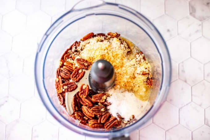 Photo of pecans, sugar, coconut, and butter in a food processor.