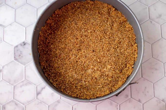Photo of a pecan crust in a springform pan.