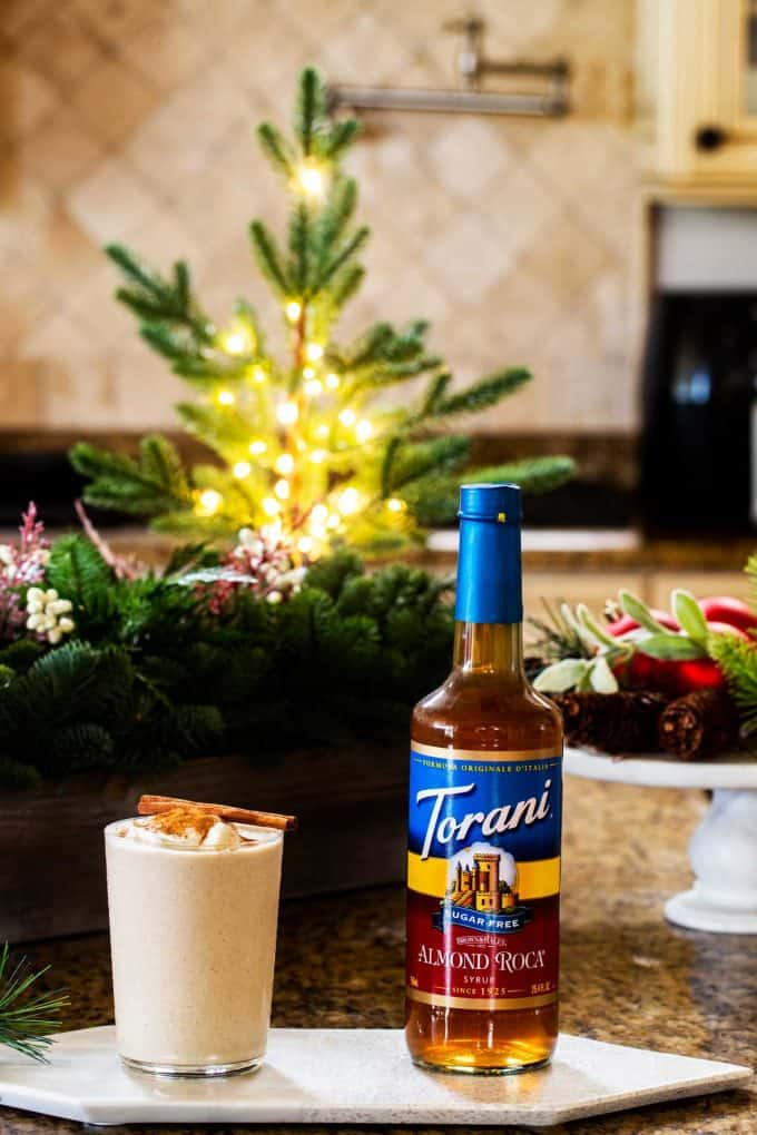 Photo of sugar free eggnog and torani syrup in a kitchen with holiday decorations behind them.