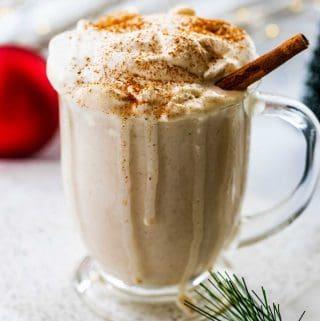 Mug of sugar free eggnog with holiday decorations and lights surrounding.