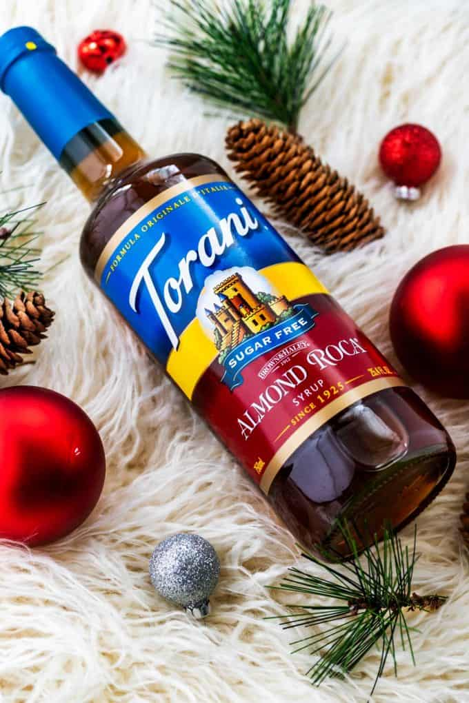 Overheat photo of Torani Sugar Free Almond Roca Syrup surrounded by holiday decorations.