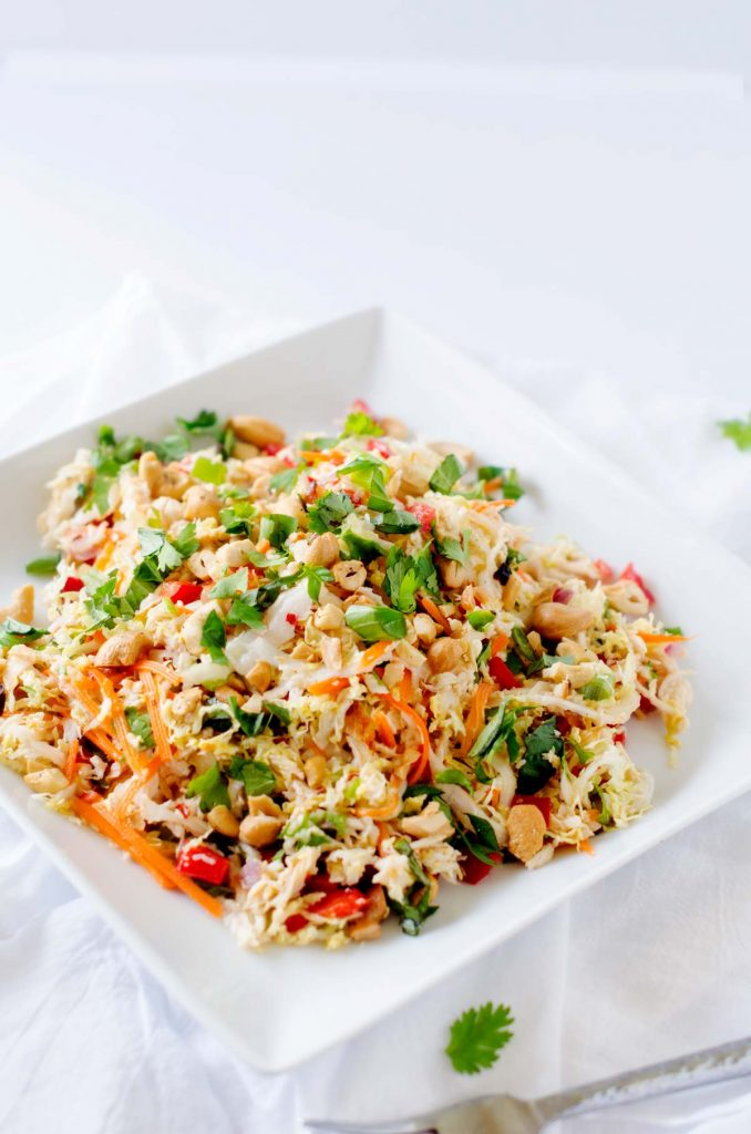 Photo of a Thai Chicken Salad with ginger lime dressing on a white plate against a white background.