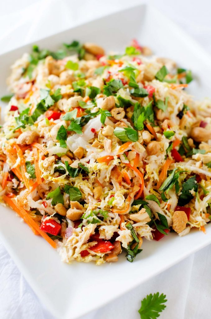Close up photo of a thai chicken salad on a white plate.