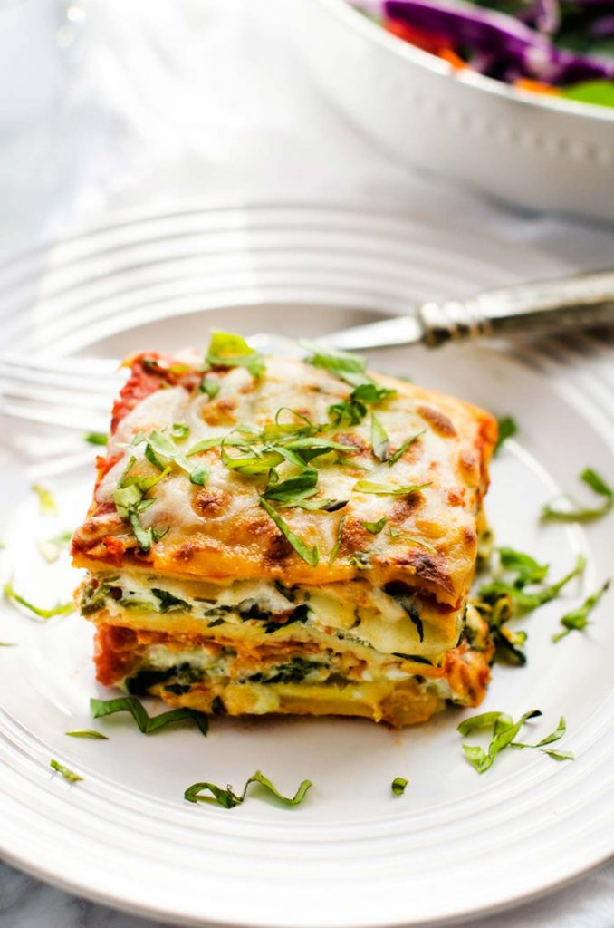 ¾ overhead photo of a white plate with gluten free vegetarian lasagna on it.