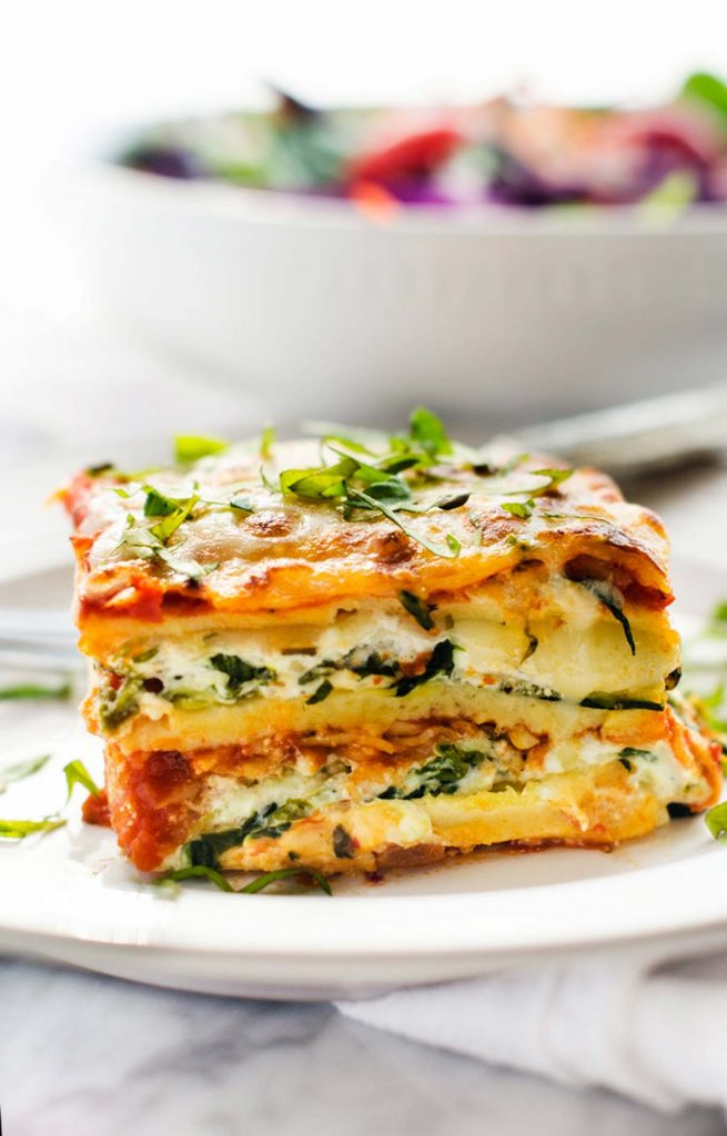 Side photo of gluten free vegetarian lasagna with a salad in a bowl behind it.