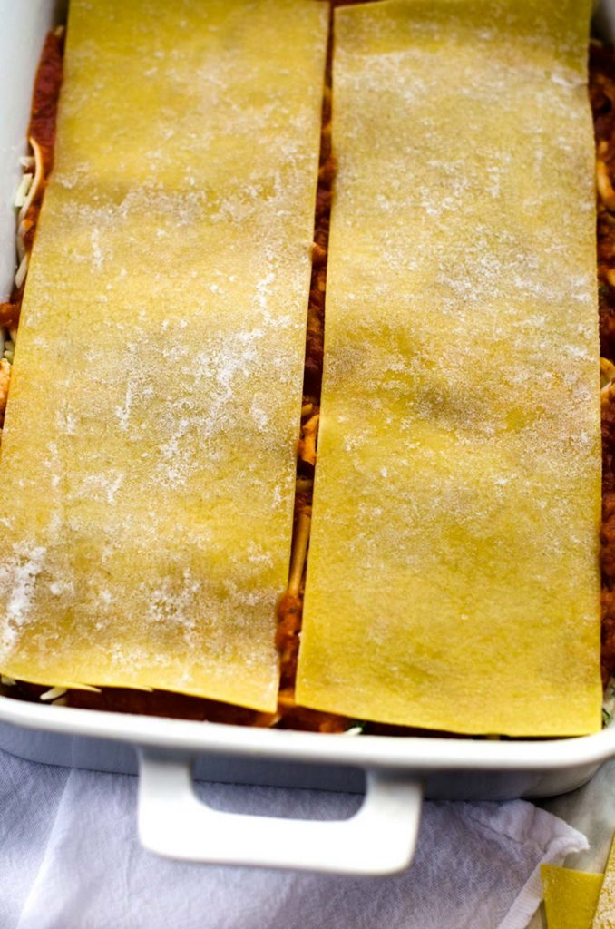 Photo of gluten free noodles being added to lasagna.
