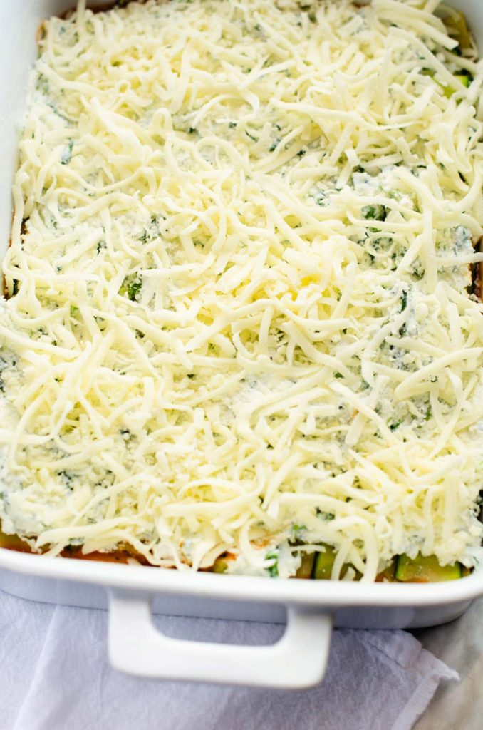 Photo of a casserole dish of lasagna with grated cheese on top.