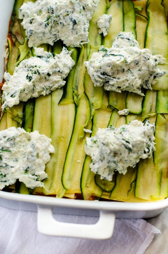 Photo of a ricotta cheese mixture that has been dolloped over zucchini noodles.