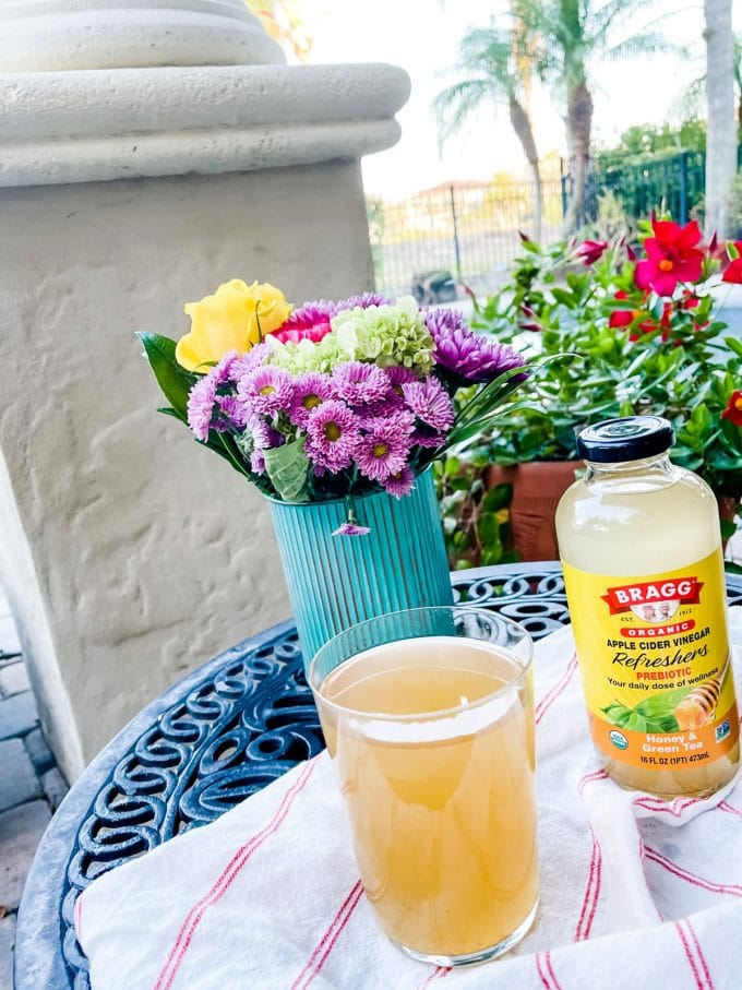Photo of Bragg Refreshers sitting on an outdoor table with flowers around it.