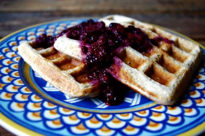 Photo of quinoa waffles on a blue plate with blackberry sauce.