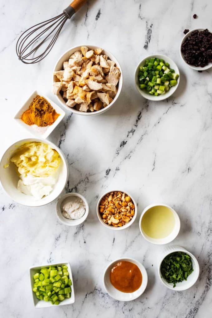 Ingredients for Healthy Curry Chicken Salad in white prep bowls on a white background.