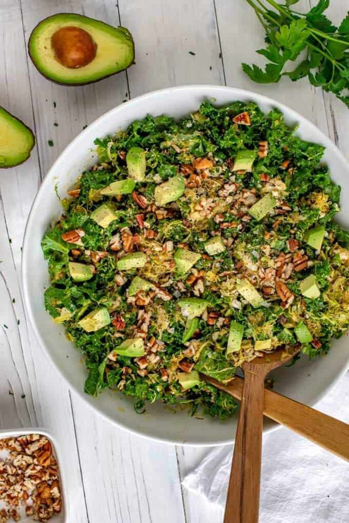 Two salad serving utensils in a white bowl with Kale Brussels Sprout Salad.
