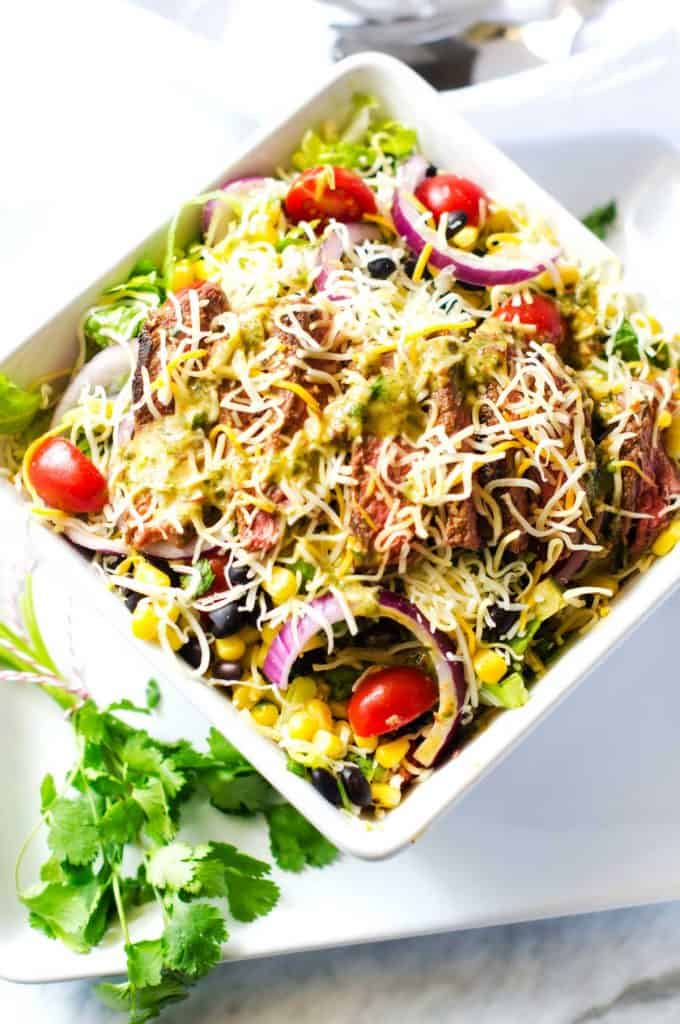 Overhead photo of a Mexican Steak Salad in a large white bowl on a white platter.