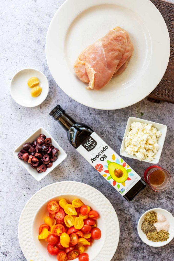 A bottle of avocado oil and plate of raw chicken breast surrounded by prep bowls of garlic, olives, tomatoes, seasonings, broth, and feta.