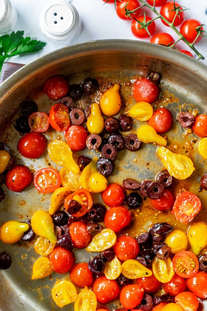 Photo of garlic, broth, tomatoes, and olives in a large skillet.