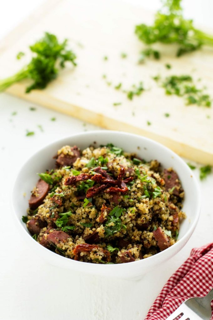 Bowl of Sausage Quinoa with a cutting board with parsley behind it.