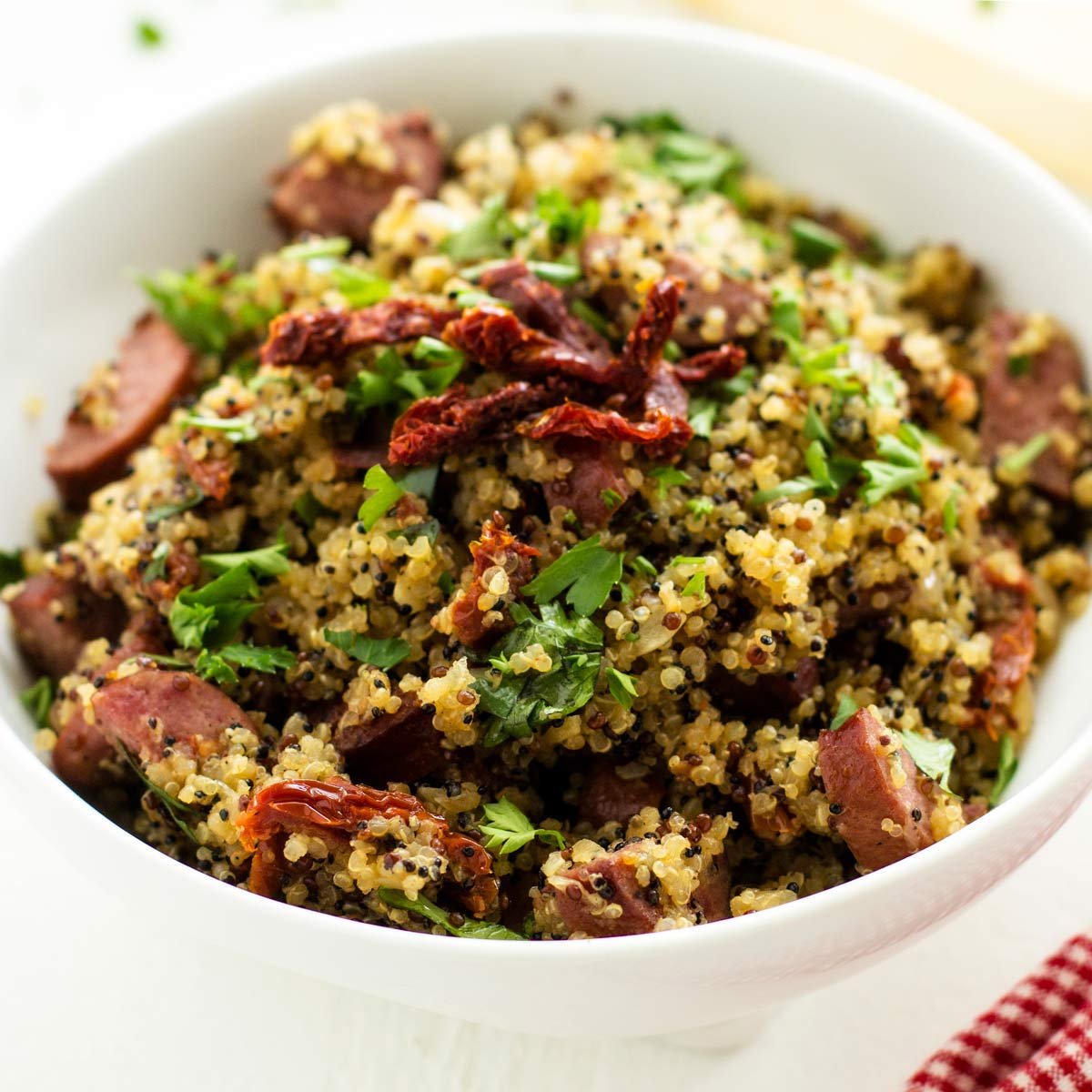 Square close up photo of a white bowl with quinoa and sausage garnished with parsley and sun dried tomatoes.