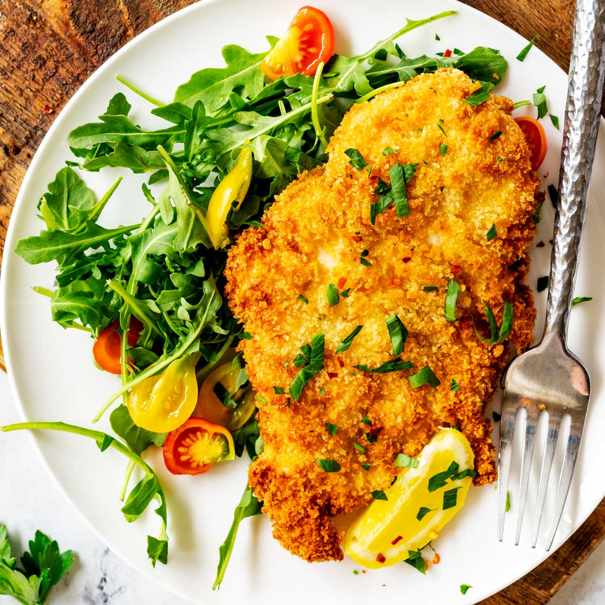 Square overhead photo of a white plate with air fryer chicken cutlets and and salad on a dark cutting board.