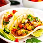 Square photo of two slow cooker chicken fajitas on a white plate garnished with cilantro and jalapeno.