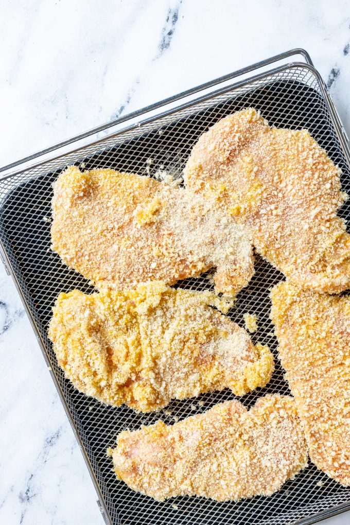 Photo of an air fryer tray with air fryer chicken cutlets ready to be cooked.