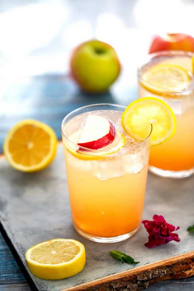 Photo of two glasses of an apple shrub recipe surrounded by lemons and apples.