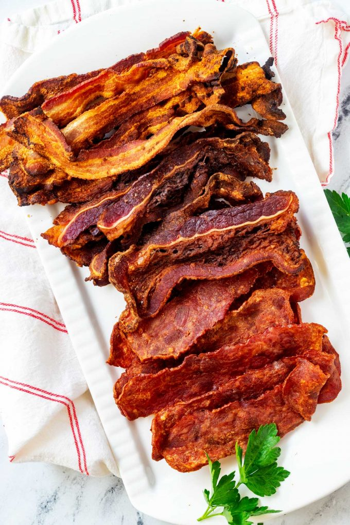 Overhead photo of Ninja Foodi Grill Bacon on a large white platter.  Photo has pork, beef, and turkey bacon.