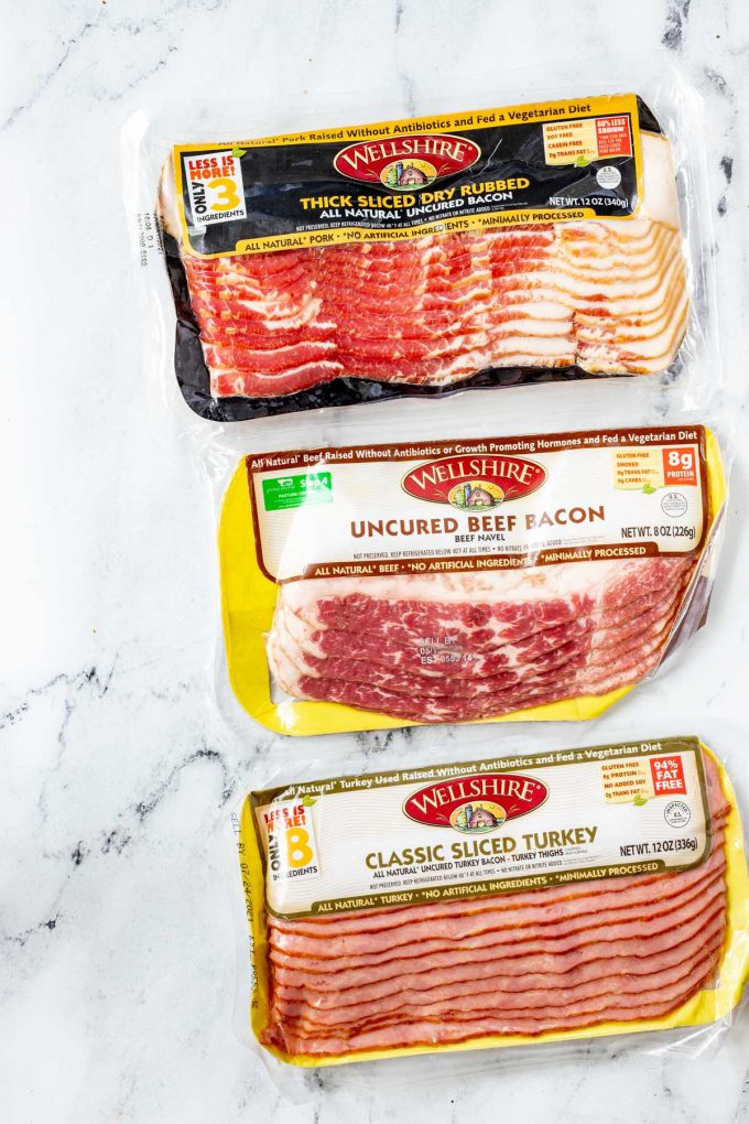 Packages of pork bacon, beef bacon, and turkey bacon.