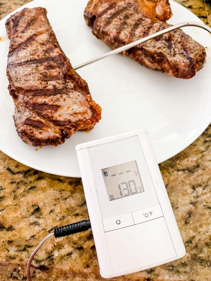 I photo of a thermometer in steaks registering 130 degrees.