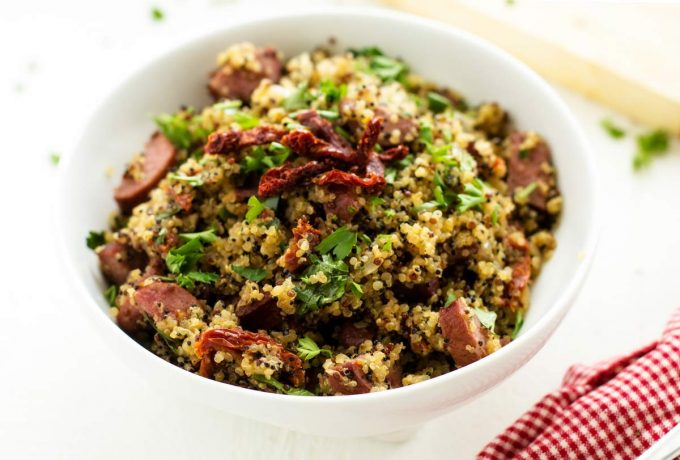 Close up photo of a white bowl with quinoa and sausage garnished with parsley and sun dried tomatoes.