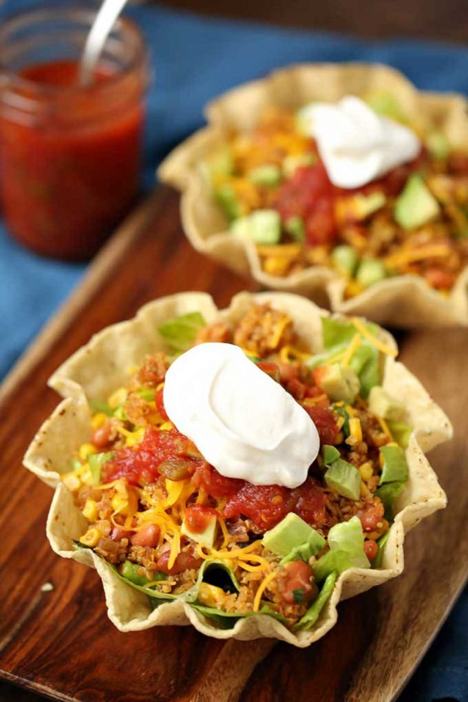 Photo of two bowls of Quinoa Taco Salad on a cutting board.