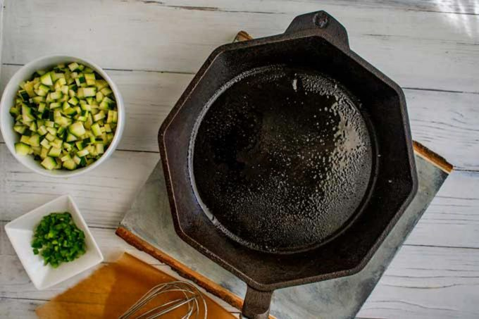 Photo of a cast iron skillet sprayed with oil and bowls of diced vegetables next to them.