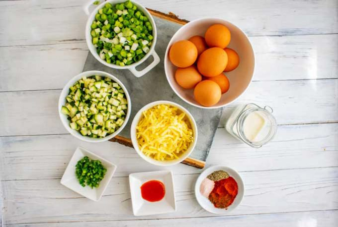 Photo of prep bowls with eggs, scallions, zucchini, jalapeno, shredded cheddar, hot sauce, seasonings, and cream.