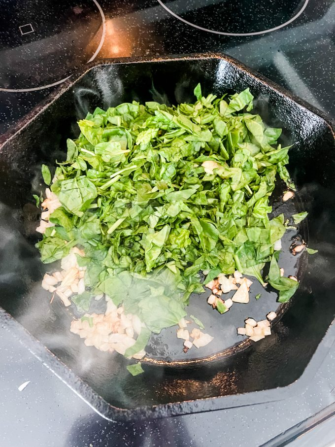 Photo of spinach that has been added to onions in a skillet.