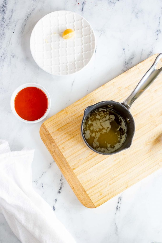Photo of butter melted in a small saucepan with a clove of garlic and buffalo sauce in prep containers beside it.