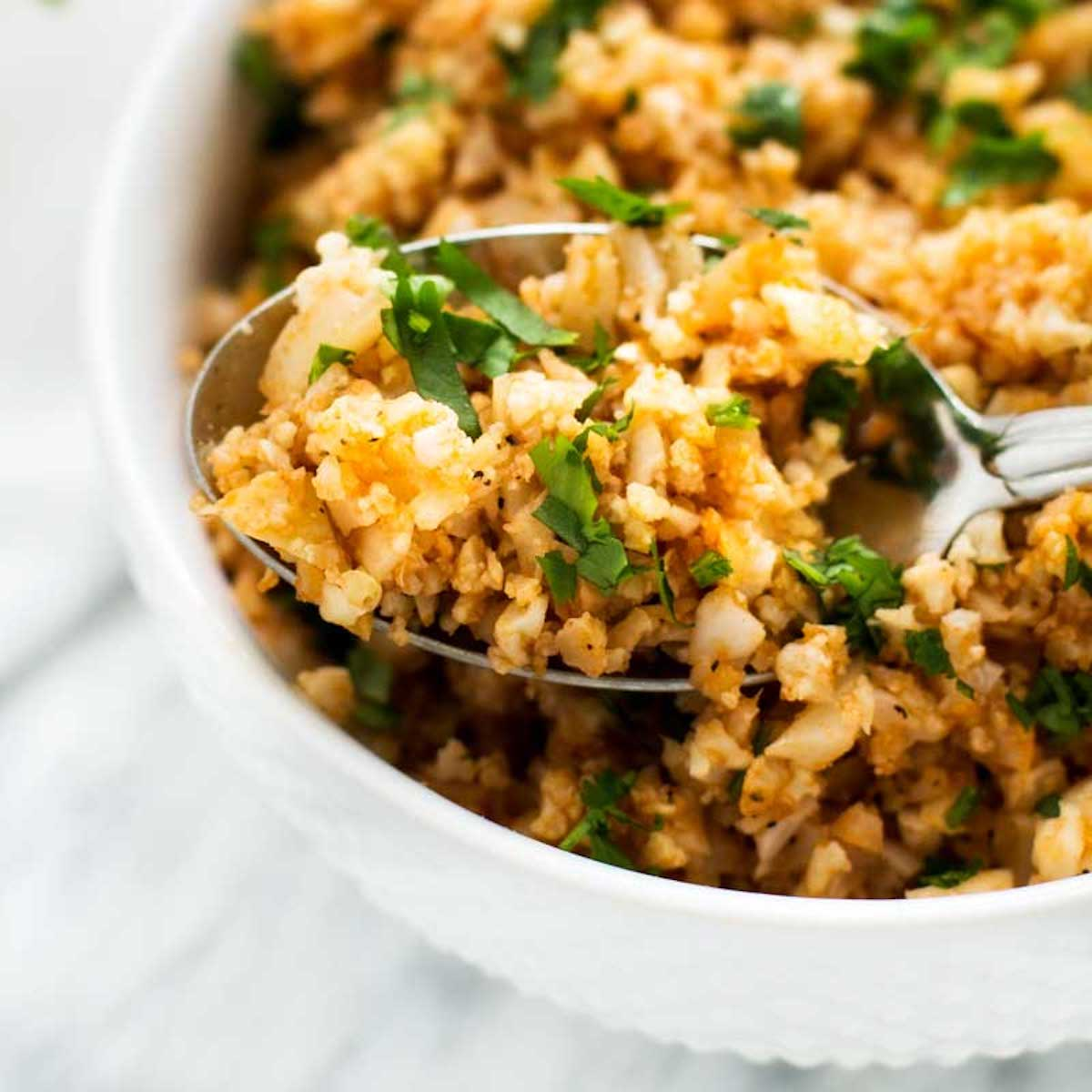 Close up photo of a spoonful of Spanish Cauliflower Rice resting in a bowl of keto rice.